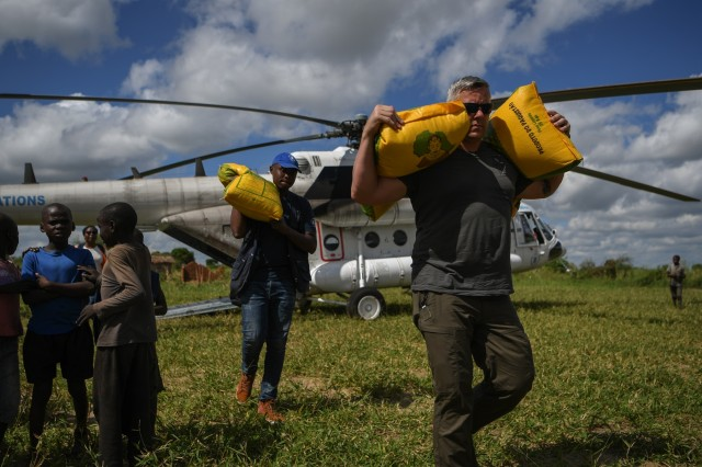 U.S. Army Maj. Eric Buendia, assigned to Combined Joint Task Force - Horn of Africa (CJTF-HOA), helps unload humanitarian aid from a World Food Programme helicopter in Bebedo, Mozambique, April 8, 2019, during humanitarian relief efforts in the Republic of Mozambique and surrounding areas following Cyclone Idai. Teams from CJTF-HOA, which is leading U.S. Department of Defense support to relief efforts in Mozambique, began immediate preparation to respond following a call for assistance from the U.S. Agency for International Development's Disaster Assistance Response Team. (U.S. Air Force photo by Staff Sgt. Corban Lundborg)