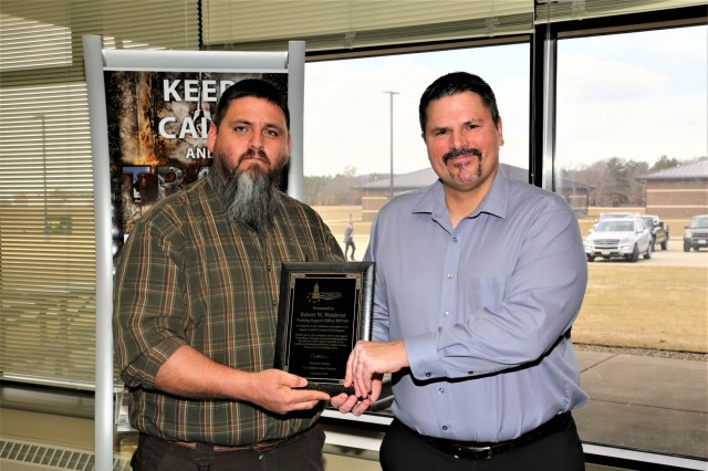 "William ""Bo"" Pearson with the Tomah (Wis.) Veterans Affairs (VA) Medical Center presents a special appreciation award April 3, 2019, to Training Support Officer Rob Weisbrod with the Directorate of Plans, Training, Mobilization and Security at building 220 at Fort McCoy, Wis. Weisbrod, along with other members of DPTMS, were recognized by VA providers with the Combat Residential Post-Traumatic Stress Disorder Program at the medical center for starting a treatment project for patients at Fort McCoy. (U.S. Army Photo by Scott T. Sturkol, Public Affairs Office, Fort McCoy, Wis.)"