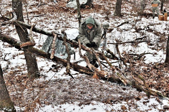 A student in Fort McCoy's Cold-Weather Operations Course (CWOC) Class 19-02 works on building an improvised shelter Jan. 17, 2019, at a remote location on South Post at Fort McCoy, Wis. CWOC students are trained on a variety of cold-weather subjects, including snowshoe training and skiing as well as how to use ahkio sleds and other gear. Training also focuses on terrain and weather analysis, risk management, cold-weather clothing, developing winter fighting positions in the field, camouflage and concealment, and numerous other areas that are important to know in order to survive and operate in a cold-weather environment. The training is coordinated through the Fort McCoy Directorate of Plans, Training, Mobilization and Security. (U.S. Army Photo by Scott T. Sturkol, Public Affairs Office, Fort McCoy, Wis.)