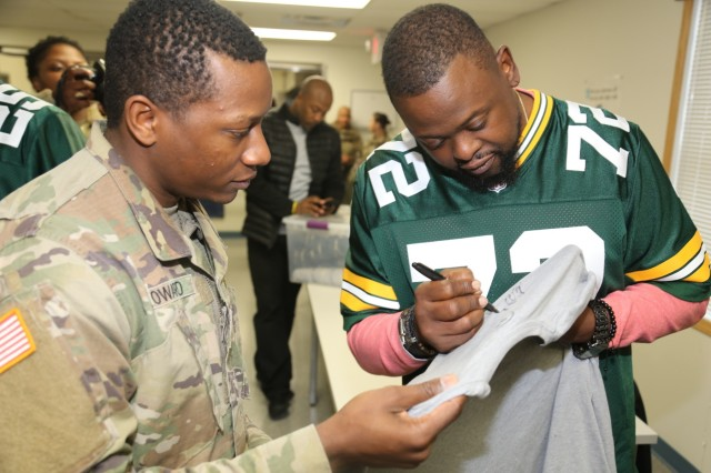 Packers alumni Earl Dotson with the Green Bay Packers Tailgate Tour signs an autograph for a Soldier at a dining facility April 10, 2019, at Fort McCoy, Wis. Packers President/CEO Mark Murphy and six Packers alumni were among the people on the 14th annual Packers Tailgate Tour who visited Fort McCoy. Packers alumni on the tour were Dotson, Nick Barnett, Ryan Grant, Aaron Kampman, Scott Wells, and Bernardo Harris. All of the tour members mingled with Soldiers, signed autographs, and posed for photos. Tour members also visited Fort McCoy's Range 2 to learn about operations for Operation Cold Steel III and Task Force Fortnite. (U.S. Army Photo by Scott T. Sturkol)