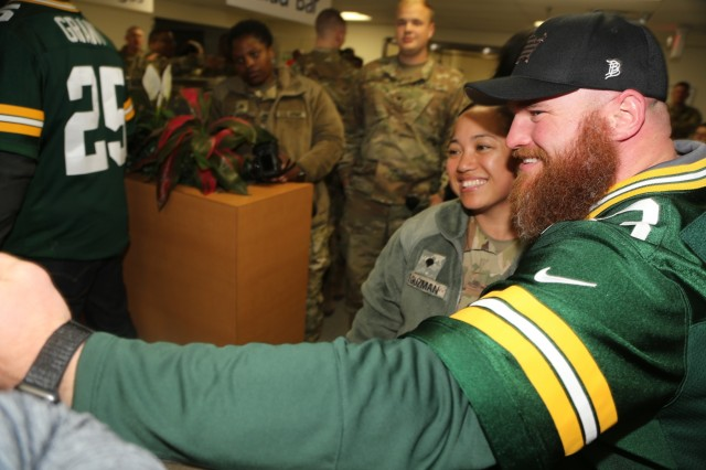Packers alumni Scott Wells with the Green Bay Packers Tailgate Tour takes a photo with a Soldier at a dining facility April 10, 2019, at Fort McCoy, Wis. Packers President/CEO Mark Murphy and six Packers alumni were among the people on the 14th annual Packers Tailgate Tour who visited Fort McCoy. Packers alumni on the tour were Dotson, Nick Barnett, Ryan Grant, Aaron Kampman, Wells, and Bernardo Harris. All of the tour members mingled with Soldiers, signed autographs, and posed for photos. Tour members also visited Fort McCoy's Range 2 to learn about operations for Operation Cold Steel III and Task Force Fortnite. (U.S. Army Photo by Scott T. Sturkol)