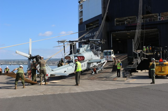 Marines load a Cobra helicopter onto the M/V Green Lake during port operations at Pearl Harbor on March 30.