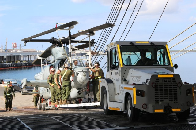Marines the front end of a Cobra helicopter to  counter-balance it as they load it onto the M/V Green Lake during port operations at Pearl Harbor on March 30.