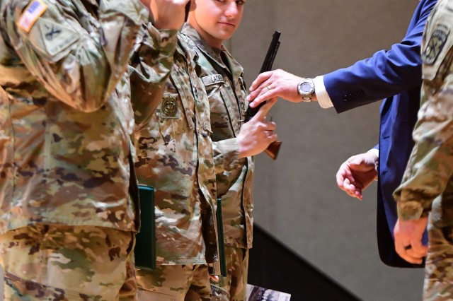 'Still learning' -- Pfc. Tony Ladebu, the 2019 Soldier of the Year for U.S. Army Cadet Command, takes cues from the NCOs of the Year on how to hold his prized pistol during the awards ceremony. Each winner received a pistol, Trojan helmet and gift prizes for their efforts.