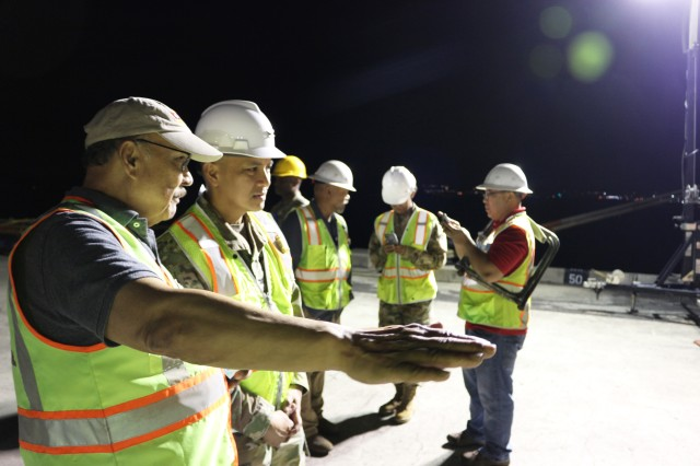 From left: Francis Nazareth, Central Gulf Lines vice president for operations, and Col. Frazariel Castro, 599th Transportation Brigade commander, discuss the offload during nighttime port operations at Pearl Harbor on March 29.