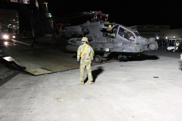 A tug offloads an Apache helicopter from the M/V Green Lake during nighttime port operations at Pearl Harbor on March 29.