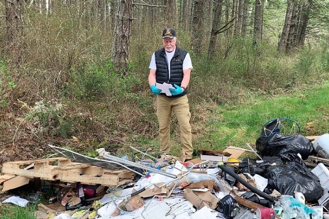 "Greg Mason, an environmental investigator from the Joint Base Lewis-McChord's Directorate of Public Works, examines documents found during the search of an illegal dump site April 2. Better known as JBLM's ""Trash Cop,"" Mason has been investigating illegal dump sites on JBLM since 2005 in an effort to help the base recoup clean-up costs."