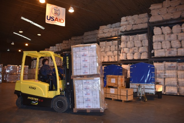 Carmensita Caroccia, warehouse worker and fork lift operator, 405th Army Field Support Battalion, Africa, moves supplies inside the Office of Foreign Disaster Assistance warehouse at Camp Darby. The emergency supplies were shipped to Mozambique in support of those devastated by Cyclone Idai in late March.