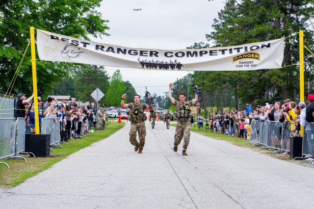 First Lts. Eric von Kuhn, left, and Nathan Penick, right, representing the 101st Airborne Division, cross the finish line of the buddy run. After two full days and nights of events to test their stamina, technical prowess and mental acuity, 16 teams crossed the finish line April 14 at Camp Rogers, concluding the Best Ranger Competition.