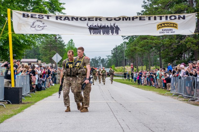 Capts. Michael Rose, left, and John Bergman, right, of Team 19, representing the 101st Airborne Division, finish the final buddy run. After two full days and nights of events to test their stamina, technical prowess and mental acuity, 16 teams crossed the finish line April 14 at Camp Rogers, concluding the Best Ranger Competition.