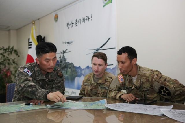 ROKA Col. Kim, Seong-jong, ROKA 13th Aviation Group commander, U.S. Army Chief Warrant Officer 2 Johnta Daniels (right), Jacksonville, Florida native, and Warrant Officer 1 Bradley R. Fuller (center), Mary Falls, California native, both UH-60 Blackhawk pilots with 2-2 Assault Helicopter Battalion, 2nd Combat Aviation Brigade, 2nd Infantry Division/ROK-U.S. Combined Division, discuss the scheme of maneuver to effectively contain and extinguish the wildfire in Gangwon province, northeast of Seoul, April 5. (Courtesy photo by Republic of Korea Army Public Affairs)
