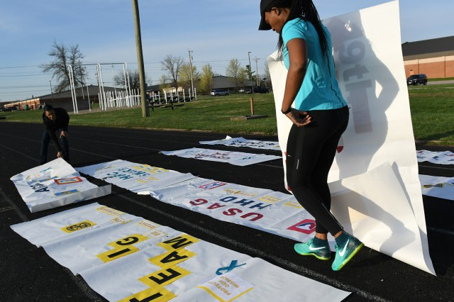 Sgt. Adriane King lays out competing unit's banners for the inaugural commencement ceremony of the 2019 SHARP Cup Field Meet.  The teams competed against each other in multiple physical activities to include a spirited kickball tournament while other team members contributed with points earned for correct answers to SHARP-related questions.