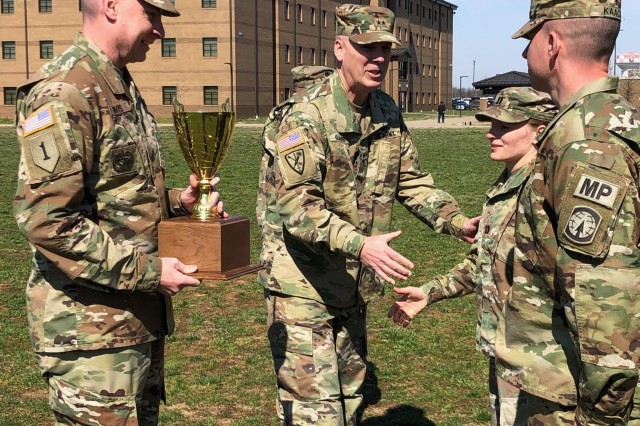 Sgt. Maj. Larry Orvis (left), Army Provost Sgt. Maj., holds the J.P. Holland Award trophy as Maj. Gen. David Glaser (middle), Provost Marshal General, congratulate the 551st Military Police Company command team, Capt. Katie Troxell (middle right), commander, and 1st Sgt. Jason Kaack (far right), senior enlisted advisor for 551st MP Co., for receiving the award. (Photo by 1st Lt. Matthew Murphy, 551st MP Co. UPAR)