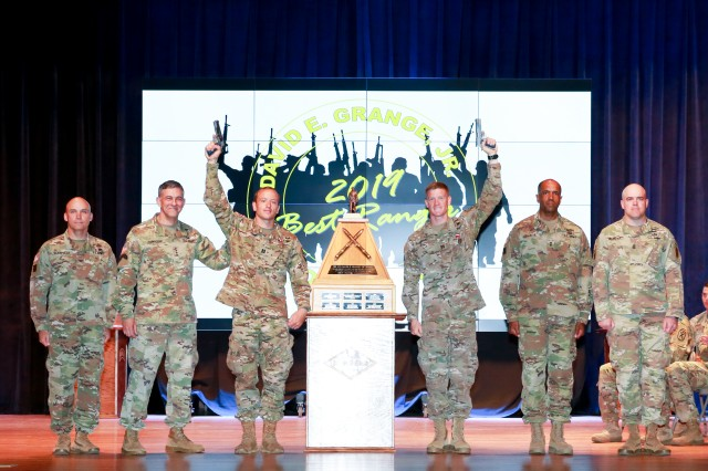 """Capts. Michael Rose, center left, and John Bergman, center, right, hold pistols above them after winning the 2019 Best Ranger Competition here April 15. Bergman and Rose of the 101st Airborne Division at Fort Campbell, Ky., earned the title of """"Best Rangers"""" during an awards ceremony at the Maneuver Center of Excellence headquarters April 15 at Fort Benning. Rose is the first ranger to win three times, and Rose and Bergman are the first team members to win together twice. Bergman and Rose won together in 2014 when they were second lieutenants representing the 25th Infantry Division at Schofield Barracks, Hawaii, and Rose won again in 2017 when he represented the 75th Ranger Regiment with Master Sgt. Josh Horsager."""