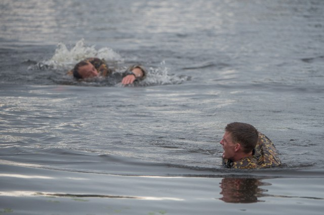 """Capts. Michael Rose, left, and John Bergman swim across Victory Pond April 12 during the 2019 Best Ranger Competition. Bergman and Rose of the 101st Airborne Division, Fort Campbell, Ky., earned the title of """"Best Rangers"""" during an awards ceremony at the Maneuver Center of Excellence headquarters April 15 at Fort Benning. Rose is the first ranger to win three times, and Rose and Bergman are the first team members to win together twice. Bergman and Rose won together in 2014 when they were second lieutenants representing the 25th Infantry Division at Schofield Barracks, Hawaii, and Rose won again in 2017 when he represented the 75th Ranger Regiment with Master Sgt. Josh Horsager."""