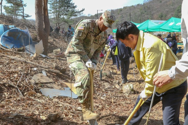 Lt. Col. Shane R. Doolan, Brooklyn, New York, deputy commanding officer, 210th Field Artillery Brigade, 2nd Infantry Division/ROK- U.S. Combined Division, prepares to plant trees alongside Dongducheon City Mayor Choi, Yong-deuk during the 74th Annual City Hall Arbor Day celebration at Tapdong Elementary School, April 5, 2019, Dongducheon, Republic of Korea. While supporting U.S. Forces Korea's Good Neighbor Program, 210th FAB Soldiers and DDC citizens planted trees together to help enhance friendships and strengthen the ROK-U.S. Alliance. (U.S. Army photo by KATUSA Cpl. Jang, Taemin)