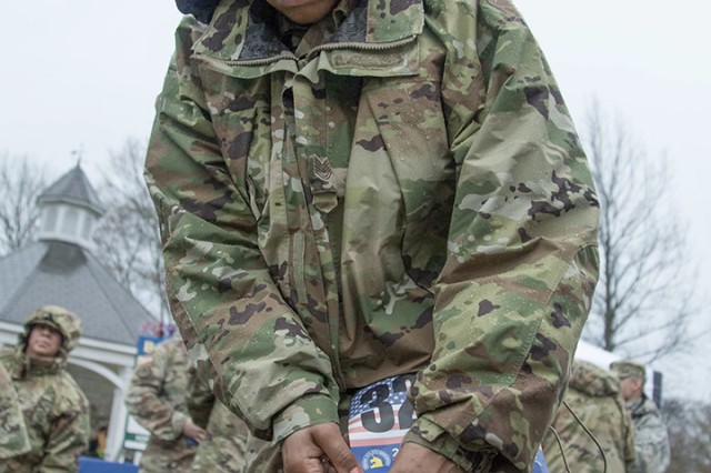 Air Force Tech. Sgt. Shavonne Hinds pins a Boston Marathon race bib to her leg.