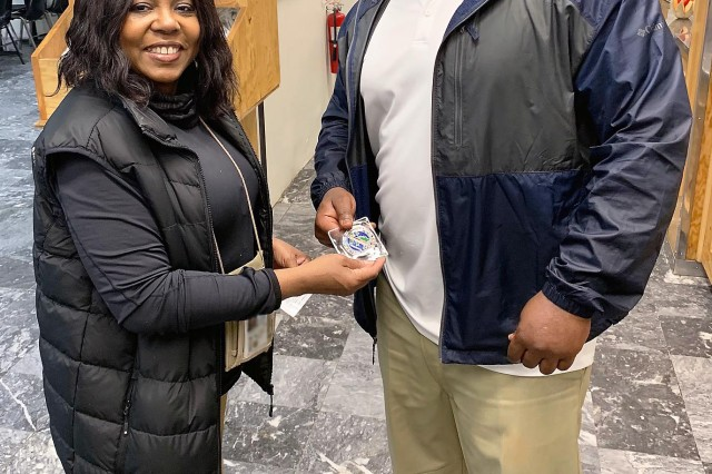Charmane Johnson, program manager for Combat Trafficking in Persons, U.S. Forces -- Afghanistan and U.S. Central Command, awards Courtney Fields, dining facility manager at Forward Operating Base Fenty, Afghanistan, with a DOD CTIP coin for his facility's support in displaying CTIP posters during a battlefield circulation. (Photo by Nichelle Fails, USFOR-A SAPR)