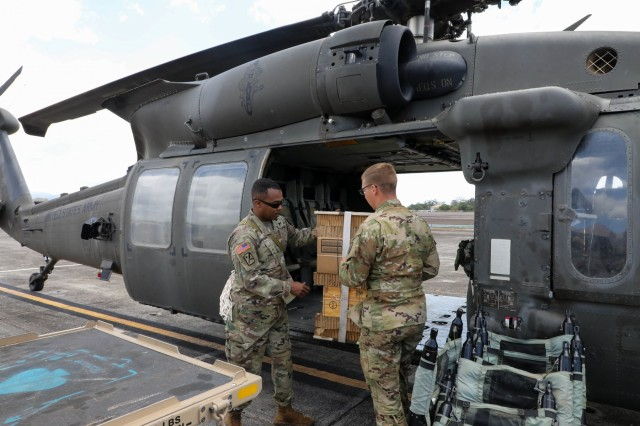 Spc. Austin Gutherman, Crew Chief assigned to 25th Combat Aviation Brigade and Chief Warrant Officer 3 Gregory Benson, Airdrop Systems Technician assigned to 25th Division Sustainment Brigade, load rigged airdrops of 390lbs of meals and ammunition; approximately one day worth from four UH-60 Black Hawk helicopters to drop from two locations simultaneously. (U.S. Army Photos by Sgt. SarahD Williams)