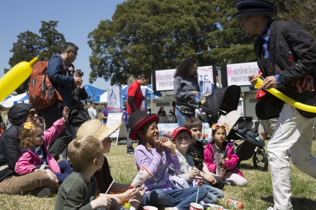 """Children talk to a balloon artist during the sixth annual children's festival, known in Japanese as the """"Kodomo no Matsuri,"""" held April 13 at Dewey Park at Camp Zama, Japan. Camp Zama's Child and Youth Services hosted the event to celebrate and kick off the Month of the Military Child."""