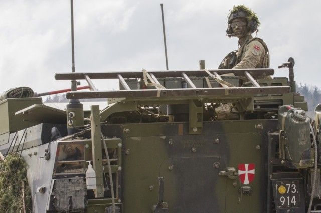 A service member from the Danish military looks to ensure roads are clear during Allied Spirit X at Hohenfels Training Area, Germany, April 06, 2019. Allied Spirit is a U.S. Army Europe-directed multinational exercise series designed to develop and enhance NATO and key partner interoperability and readiness across specified warfighting functions.