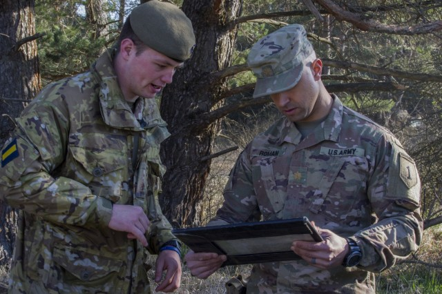 U.S. Army Maj. Widmar Roman, operations officer with 2nd Battalion, 34th Armored Regiment, 1st Armored Brigade Combat Team, 1st Infantry Division, looks over a map with an officer from the United Kingdom military during Allied Spirit X at Hohenfels Training Area, Germany, April 06, 2019. Allied Spirit is a U.S. Army Europe-directed multinational exercise series designed to develop and enhance NATO and key partner interoperability and readiness across specified warfighting functions.