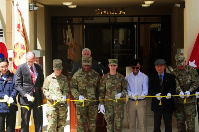 Pfc. Morgan Villarreal, radiology specialist, 168th Multipurpose Medical Brigade, and her husband Roman Villarreal along with other distinguished guests cut the ribbon for Shilla tower signifying its official opening, April 16, 2019, Camp Walker, Republic of Korea. The Villarreals are the first of many Families to be moving into Shilla tower. (U.S. Army Photo by Pvt. Jared Kindlespire)