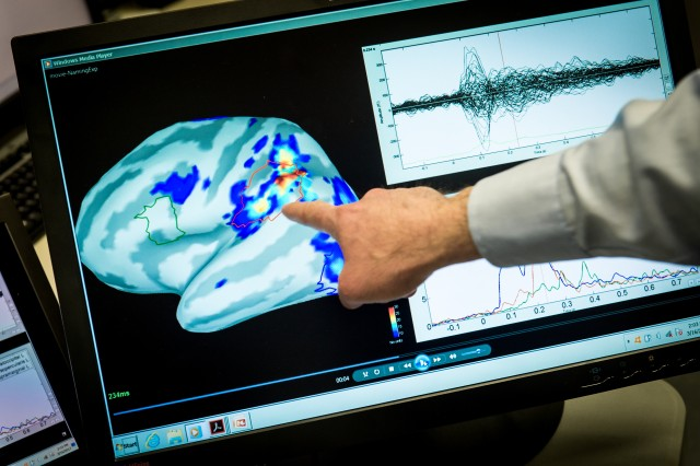 Magnetoencephalography (MEG) Laboratory scientist, Mihai Popescu points out areas of magnetic activity in a brain on a display at the National Intrepid Center of Excellence (NICoE) at Walter Reed National Military Medical Center in Bethesda, Md., March 16, 2017.