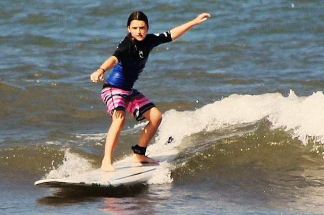 Elisabeth McCallum-Polleys, the Army's Military Child of the Year, surfs waves in Oahu, Hawaii. McCallum-Polleys faced a difficult transition after her mom, Maj. Tara McCallum received an assignment with the Detroit Arsenal in 2015.