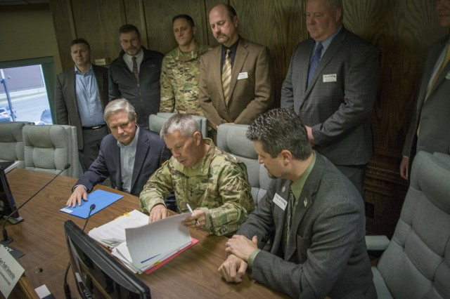 The U.S. Army Corps of Engineers Chief of Engineers and Commanding General Lt. Gen. Todd T. Semonite signs the Chief's Report, progressing a flood risk management project in Minot, North Dakota, to Congress for authorization. The signing took place after a special meeting -- held April 16 at Minot's city hall -- with Sen. John Hoeven, Col. Sam Calkins, St. Paul District commander,  city of Minot officials, the Souris River Joint Water Resource Board and representatives from various federal agencies. If the plan is approved by Congress the project would fill the gap between phases of the Mouse River Enhanced Flood Protection Plan, a local project developed after the 2011 flood that went into construction in 2018.