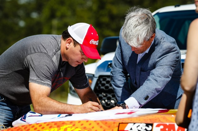 Ryan Newman, left, NASCAR driver, and Greg Walter, the executive vice president and general manager of Charlotte Motor Speedway, sign a U.S. Army flag to be presented to the paratroopers of 2nd Brigade Combat Team, 82nd Airborne Division, during a military appreciation day event at Fort Bragg, N.C., April 17, 2019. NASCAR unveiled a racecar with the name of fallen Soldier Sgt. James Nolen stenciled on the windshield as part of the military appreciation day. Nolen was killed in action during his 2009 deployment to Afghanistan. (U.S. Army photo by Pfc. Hubert D. Delany III/ 22nd Mobile Public Affairs Detachment)