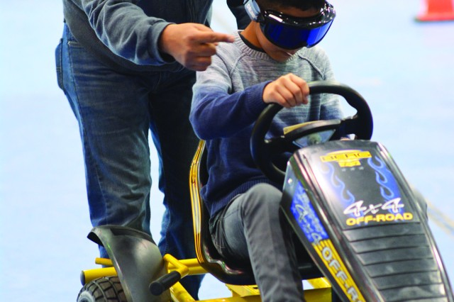 Jose Martinez helps his son, Benjamin, 10, drive a pedal car through a slalom course while wearing goggles to simulate the effects of driving impaired during the summer Safety Symposium.