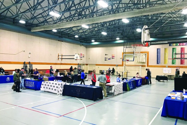 Business and education representatives speak with attendees of the Youth Hiring and Education Fair sponsored by Child and Youth Services March 30 at the CYS Teen Center.