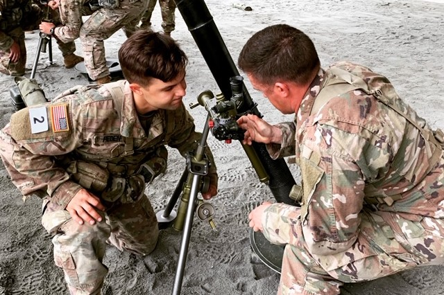 Staff Sgt. Bumgarner and Cpl. Peden from Headquarters and Headquarters Company, 2nd Battalion, 70th Armor Regiment, 2nd Armored Brigade Combat Team, 1st Infantry Division, conduct a gunner's exam on the 81-mm mortar system at The Best Mortar Competition at Fort Benning, Georgia, April 11.