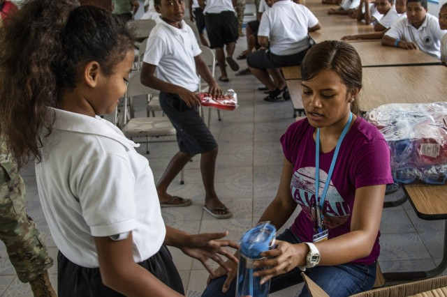Meang Ngiraingas, who serves as a budget and finance officer for the Palau Community Health Center hands out water bottles to students during a global health engagement at the Peleliu Elementary School, in Peleliu, Palau April 15, 2018, as part of Exercise Palau. The exercise is sponsored by U.S. Army Pacific and hosted by the nation of Palau, and strengthens the U.S. and Palau relationships, and contributes to a free and open Indo-Pacific. The exercise will run from April 13th - 19th 2019, and includes several security cooperation training events as well as community and animal health outreach services at several sites including Koror, Peleliu and Angaur. (U.S. Army Photo by Sgt. 1st Class Whitney C. Houston)