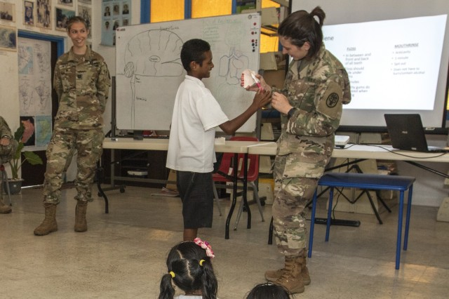 Private 1st Class Savahana Fine (right), who serves as dental assistant with Dental Activity, at Ft. Wainwright, Alaska, demonstrates proper ways to brush your teeth at Angaur Elementary School, during a global health engagement as part of Exercise Palau in Angaur, Palau April 16, 2018. Exercise Palau is sponsored by U.S. Army Pacific and hosted by the nation of Palau, and strengthens the U.S. and Palau relationships, which contributes to a free and open Indo-Pacific. The exercise will run from April 13th - 19th 2019, and includes several security cooperation training events as well as community and animal health outreach services at several sites including Koror, Peleliu and Angaur. (U.S. Army Photo by Sgt. 1st Class Whitney C. Houston)