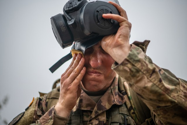 After donning his gas mask, Staff Sgt. Christian Ladd, a combat medic assigned to 1st Security Force Assistance Brigade, Fort Benning, Ga., uses a wipe to clean his skin while holding his breath during a Combat Test Lane while competing to earn his Expert Field Medical Badge.
