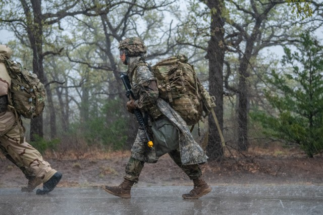 Sgt. Ashley Buhl, a combat medic assigned to 1st Battalion, 14th Field Artillery, walks through the pouring rain while competing to earn the Expert Field Medical Badge on April 6, during the EFMB Competition hosted by Reynolds Army Health Clinic.