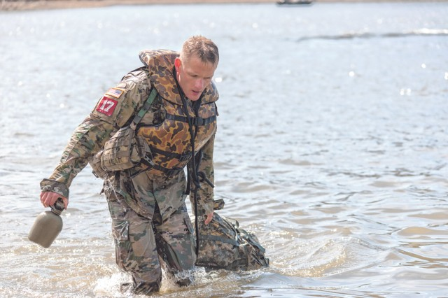 Capt. John Baer, five-time competitor in the Best Sapper Competition, drags his pack out of the water following a helocast at the Lake of the Ozarks.