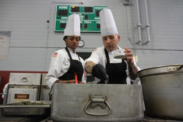 Spc. Khylissia Robertson, culinary specialist, and Staff Sgt. Carlos Mercado, advanced culinary noncommissioned officer, season courses for the mobile kitchen trailer competition March 11 during the Joint Culinary Training Exercise at Maclaughlin Fitness Center, Fort Lee, Va. The 44th annual JCTE showcases the talents of more than 200 military chefs from around the world as the largest American Culinary Federation-sanctioned competition in North America. The exercise, administered by the Joint Culinary Center of Excellence, began March 9, and ended March 14. Robertson, a St. Louis, Mo.-native serves with 2nd Battalion, 327th Infantry Regiment, 1st Brigade Combat Team, 101st Airborne Division (Air Assault). Mercado, an Isabela, Puerto Rico-native, serves in 426th Brigade Support Battalion, 1st BCT, 101st Abn. Div. (Air Assault). (U.S. Army photo by Pfc. Lynnwood Thomas, 40th Public Affairs Detachment)
