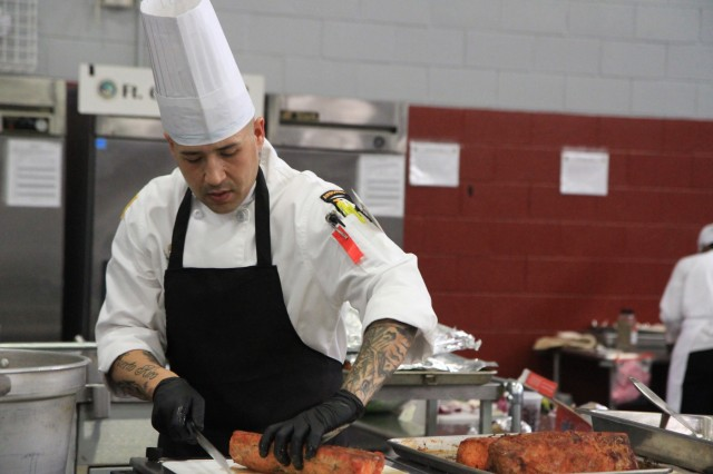Staff Sgt. Carlos Mercado, advanced culinary noncommissioned officer, slices pork loin March 11 during the Joint Culinary Training Exercise's mobile kitchen trailer competition at Maclaughlin Fitness Center, Fort Lee, Va. The Isabela, Puerto Rico-native serves in 426th Brigade Support Battalion, 1st Brigade Combat Team, 101st Airborne Division (Air Assault). The 44th annual JCTE showcases the talents of more than 200 military chefs from around the world as the largest American Culinary Federation-sanctioned competition in North America. The exercise, administered by the Joint Culinary Center of Excellence, began March 9, and ended March 14. (U.S. Army photo by Pfc. Lynnwood Thomas, 40th Public Affairs Detachment)