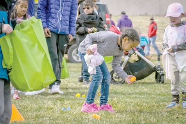 FORT CARSON, Colo. - Malisha Burns, Fort Carson Family member, picks up an Easter egg April 13, 2019, at the Fort Carson Color Fest and Creative Arts Festival at the Iron Horse Sports and Fitness Center. (Photo by Amber Martin)