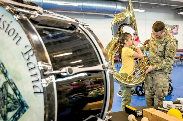 FORT CARSON, Colo. - Sgt. Jacob Conner, 4th Infantry Division Band, shows Grace Melton, Fort Carson Family member, how to play the tuba April 13, 2019, at the Carson Color Fest and Creative Arts Festival at the Iron Horse Sports and Fitness Center. (Photo by Amber Martin)