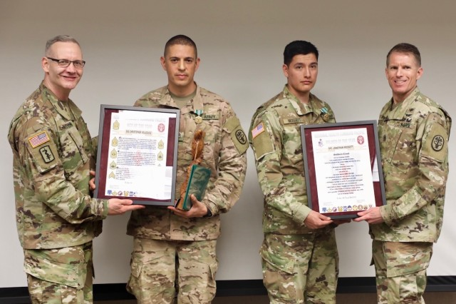 Brig. Gen. Dennis LeMaster, RHC-P commanding general, and RHC-P Command Sgt. Maj. Clark Charpentier present Staff Sgt. Christopher Velazquez and Spc. Jonathan Mossett with the NCO and Soldier's creeds at the 2019 RHC-P Best Warrior award ceremony. Velazquez won the NCO category and Mossett won the Soldier category.