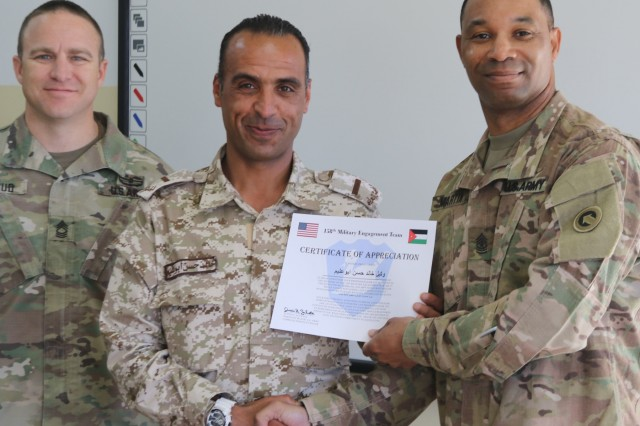 U.S. Army Sgt. Maj. Marvin Martin, 1st Theater Sustainment Command strategic operations and plans noncommissioned officer in charge, and Master Sgt. Randy Stroud, 158th Military Engagement Team, present a certificate to Jordan Armed Forces (JAF) Soldier during a non-commissioned officer exchange at the JAF Noncommissioned Officer Academy April 10, 2019. The U.S. and Jordan remain committed to a strong bilateral relationship built on shared interests and mutual respect, and the exchange focused on increasing interoperability while also identifying feasible, long-term solutions for developing JAF noncommissioned officers and improving training at the JAF NCOA.
