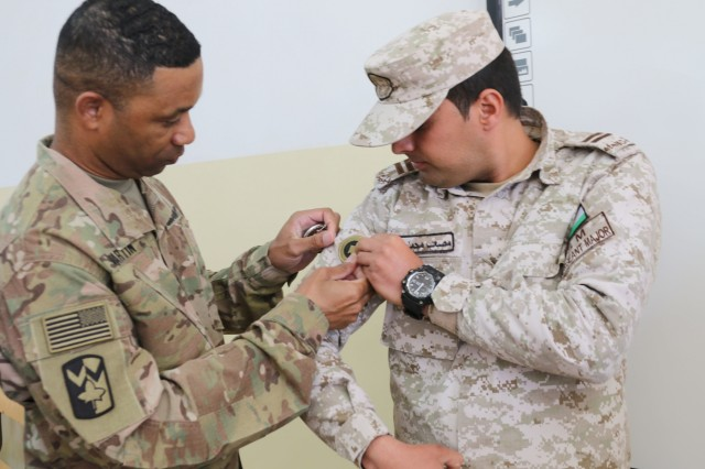 U.S. Army Sgt. Maj. Marvin Martin, 1st Theater Sustainment Command (1TSC) strategic operations and plans noncommissioned officer in charge, presents the Jordan Armed Forces NCO Academy command sergeant major with a 1TSC patch during a non-commissioned officer subject matter expert exchange at the JAF Noncommissioned Officer Academy April 10, 2019. The U.S. and Jordan remain committed to a strong bilateral relationship built on shared interests and mutual respect, and the exchange focused on increasing interoperability while also identifying feasible, long-term solutions for developing JAF noncommissioned officers and improving training at the JAF NCOA.