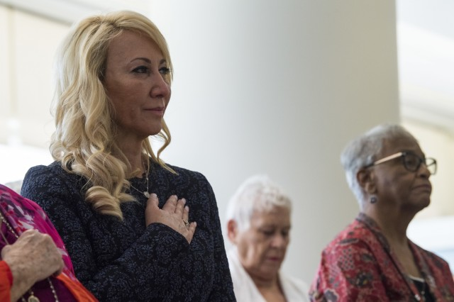Judy Hathcock, left, stands for the national anthem during a pinning ceremony, April 11, 2019, in Valdosta, Ga. George Aigen, Hathcock's father, was bestowed the highest honor in France: induction into the French Legion of Honor as a knight, or chevalier, for his actions during World War II. In April 1945, as a 19-year-old Army corporal, Aigen fought alongside other Soldiers in 1269th Combat Engineers Company B and was part of the group who liberated Dachau, the first concentration camp built by the Nazis in 1933.