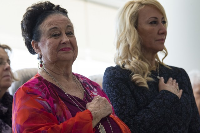 Joyce Aigen, left, and her daughter Judy Hathcock, stand for the national anthem, during a pinning ceremony, April 11, 2019, in Valdosta, Ga. George Aigen was bestowed the highest honor in France: induction into the French Legion of Honor as a knight, or chevalier, for his actions during World War II. In April 1945, as a 19-year-old Army corporal, Aigen fought alongside other Soldiers in 1269th Combat Engineers Company B and was part of the group who liberated Dachau, the first concentration camp built by the Nazis in 1933.