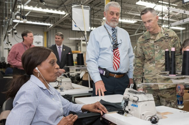 BALTIMORE - Blind Industries and Services of Maryland President Fred Puente and Aberdeen Proving Ground Senior Commander Maj. Gen. Randy Taylor look on while a BISM employee sews a garment during a tour of the Baltimore facility, April 15, 2019.