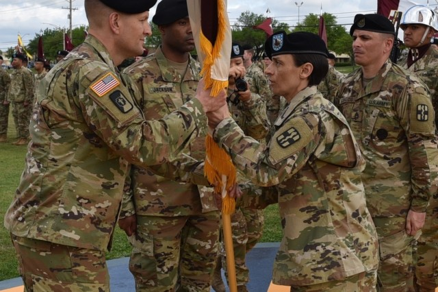 Command Sgt. Maj. Jennifer Redding, outgoing command sergeant major of the 1st Medical Brigade, passes the colors to Col. Robert Howe II, 1st MED BDE commander, during a Change of Responsibility ceremony April 18, on Cooper Field at Fort Hood, Texas.